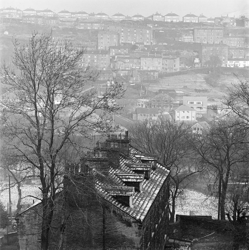 General view of the Hebble Valley, in the Denfield and Bracewell areas of Ovenden, Halifax, West Yorkshire, looking from Brackenbeds, Pellon, Halifax across towards Wheatley, showing a terrace of old stone houses in the foreground and a modern council estate on the opposite side of the valley.    1962 - 1976