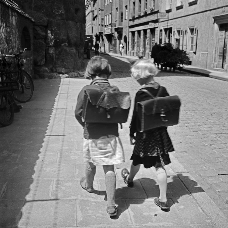 Two girls with oldfashioned backpacks walking home from school.     Date: 1930s
